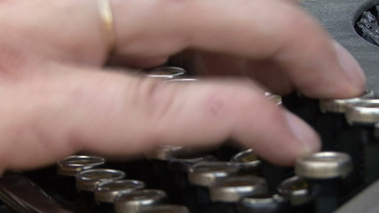 hand on a typewriter keyboard