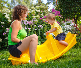 Mother sitting with her son on baby swing