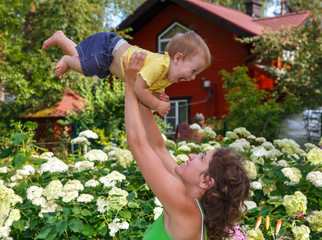Mother lifting her son high outdoors