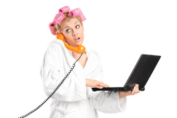 Surprised girl holding laptop and talking on phone
