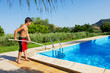 young boy retrieves objects from the pool