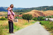 couple hitchhiking along a road