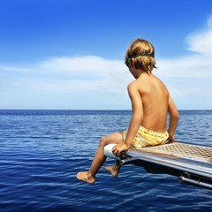 Boy sitting on boat bridge looking at the sea