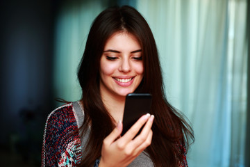 Cheerful woman using smartphone at home