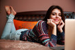 Smiling woman lying on the bed with laptop