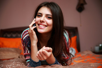 Happy beautiful woman lying on the bed and talking on the phone
