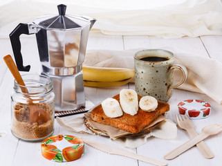 Breakfast with coffee and toast over white wooden background