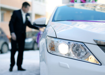 man in a suit sits in a large white car