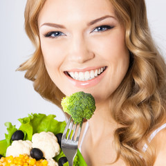 Woman with vegetarian salad, over gray