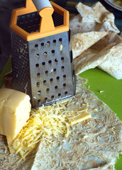 Cooking on kitchen desk. Grater, pita bread and sliced cheese