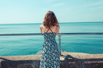 Young woman standing on a pier by the ocean
