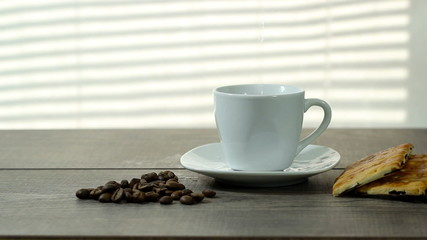 make coffee, white cup standing on a wooden table