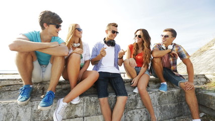group of smiling teenagers hanging out outdoors