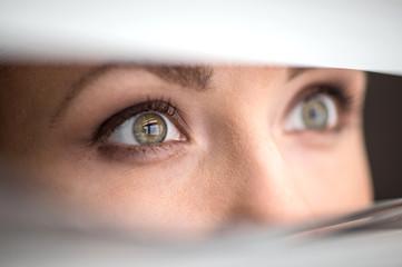 beautiful woman peeking through jalousie.
