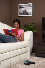 Beautiful youthful woman relaxing at home on couch.