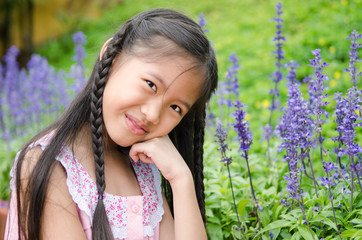 Asian little girl squat in flowers