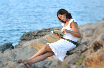 attractive 40s woman sitting alone on the beach reading a book
