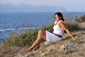 attractive 40s mature woman sitting on the beach in relax