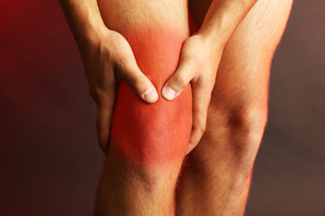 Pain concept.Young man with knee pain on dark background