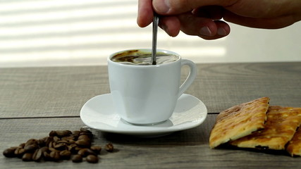 stirring coffee, a cup of coffee costs on a wooden table