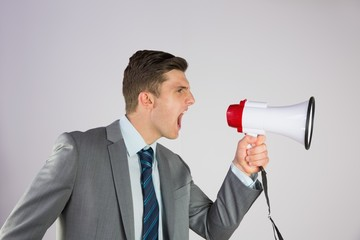 Angry businessman shouting through megaphone