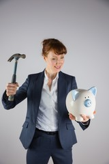 Smiling businesswoman holding hammer and piggy bank
