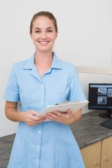Smiling dental assistant looking at camera holding clipboard