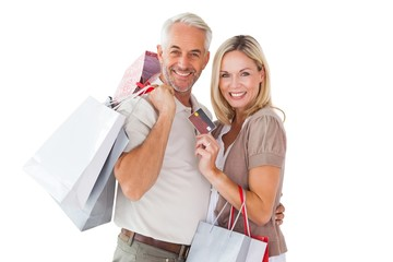 Happy couple holding shopping bags and credit card