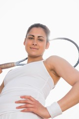Pretty tennis player holding racket smiling at camera