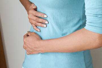 menstruation pain or stomach ache, hand holding belly closeup