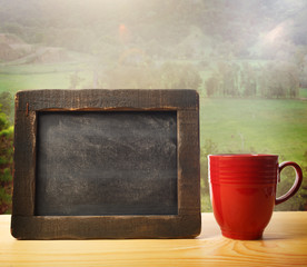 Chalkboard with red mug over country landscape