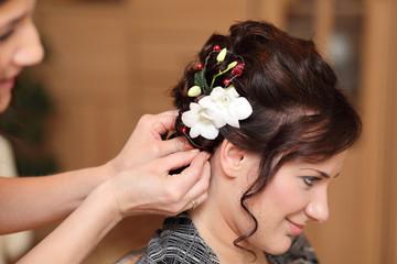 Fryzjerka wpina kwiat we włosy dziewczyny.