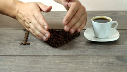 human hands making a heart shape made from coffee beans