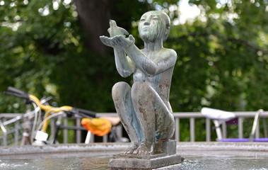 fontaine...statue d'une femme assise tenant un pigeon