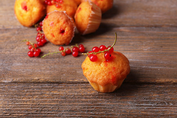 Tasty muffins with red currant on wooden background