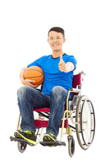 asia young man sitting on a wheelchair and thumb up