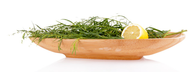 Herbs in a rectangular wooden plate isolated on white