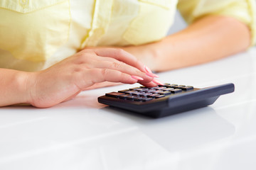 Woman's hands with a calculator
