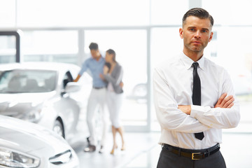 Salesman standing in car retail store. Car Showroom.