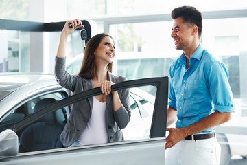 Young Couple Standing Near then New Car and Holding a Key