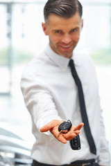 Car Salesman Giving Key of New Car at Showroom