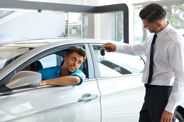 Car Salesman Handing over new Car Key to Customer at Showroom