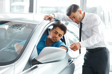 Car Sales Consultant Showing a New Car to a Potential Buyer in S