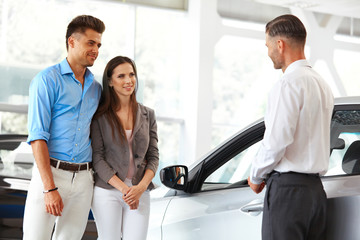 Car Showroom. Young Couple Buying a New Car at Dealership.