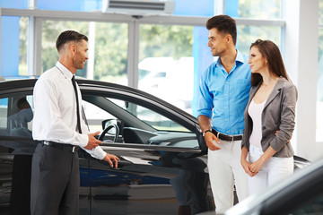 Car Showroom. Vehicle Dealer Showing Young Man New Car