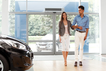 Young Couple Came into the Car Showroom. Auto Salon