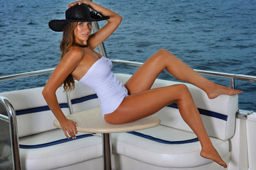 Young woman wearing swimsuit and hat relaxing on the yacht.