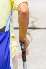 Old woman hand leans on walking stick, close-up