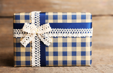 Gift box with colorful ribbon on wooden background