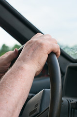 Driver's hands on the steering wheel of the car.